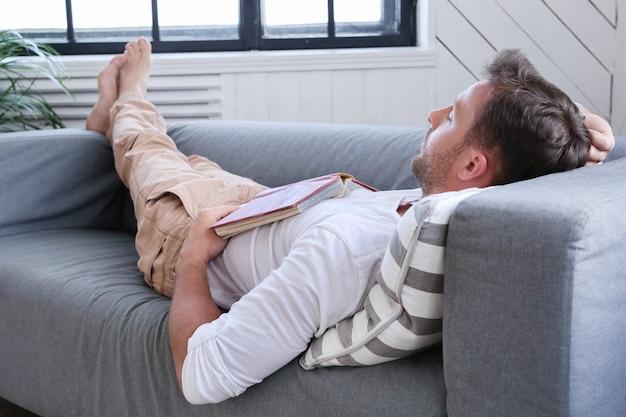 Homem bonito, dormindo no sofá com um livro