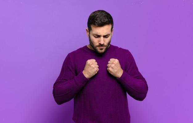 Homem bonito e adulto loiro parecendo confiante, zangado, forte e agressivo, com punhos prontos para lutar em posição de boxe
