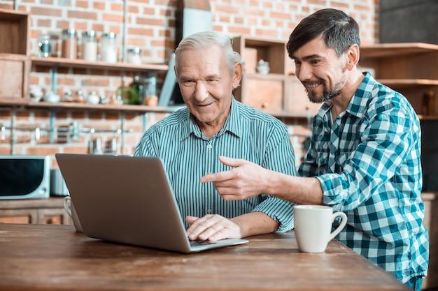 Homem bonito e agradável sentado atrás de seu pai e apontando para a tela do laptop enquanto mostra sua tecnologia moderna