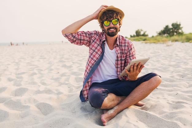 Homem bonito e alegre com barba no chapéu de palha, camisa quadriculada e óculos escuros elegantes, sentado na areia branca e usando o tablet
