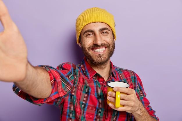 Homem bonito e alegre e sorridente estende a mão, segura uma caneca amarela, bebe café, faz uma selfie, usa chapéu e camisa xadrez