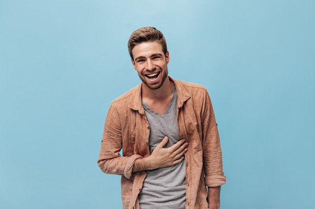 Homem bonito e alegre em uma camiseta moderna e uma camiseta legal bege, rindo e olhando para a frente na parede azul isolada