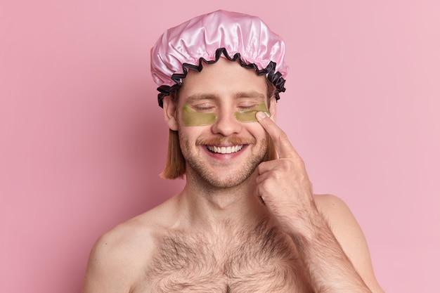 Homem bonito e alegre fecha os olhos, aponta para adesivos de hidrogel e faz tratamento para a pele