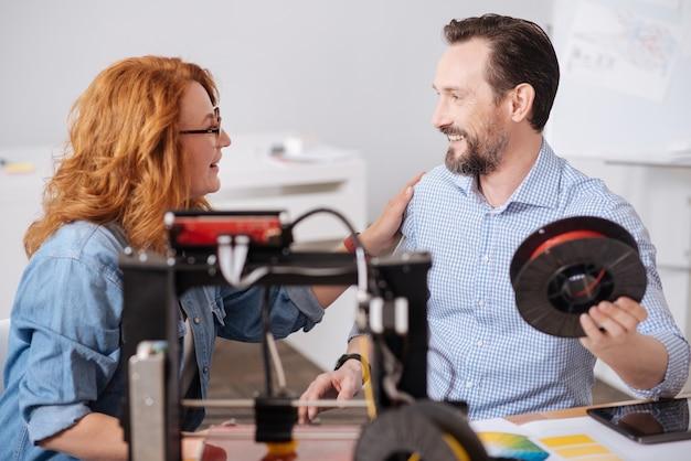 Homem bonito e alegre segurando o filamento e sorrindo enquanto olha para sua colega