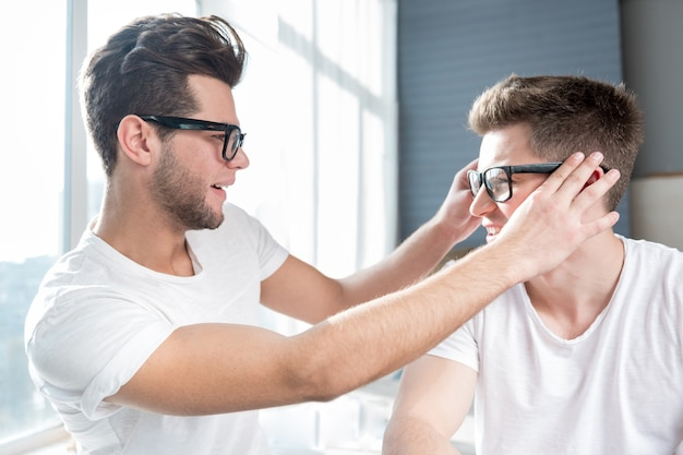Homem bonito e alegre sorrindo e tocando os óculos do namorado enquanto relaxa junto com ele perto da janela.