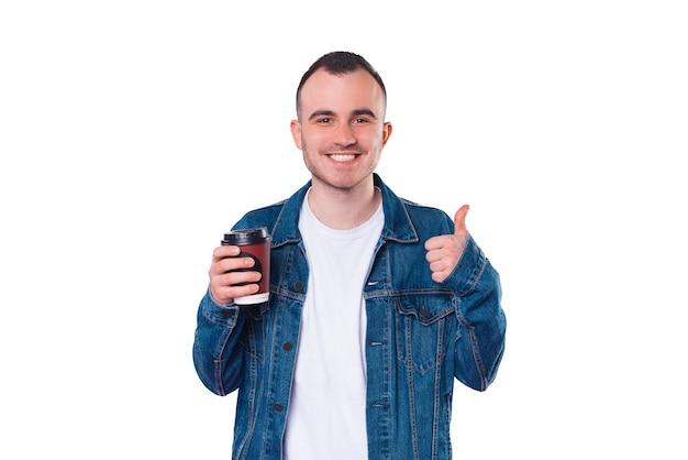 Homem bonito e alegre vestindo jaqueta jeans, segurando uma xícara de café e mostrando o polegar