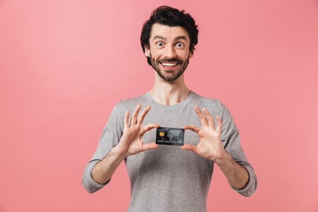 Homem bonito e animado jovem barbudo morena usando um suéter em pé rosa, mostrando o cartão de crédito