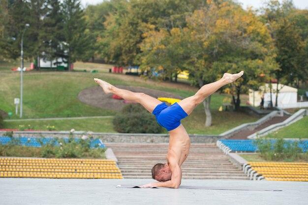 Homem bonito e atlético fazendo asanas de ioga no parque