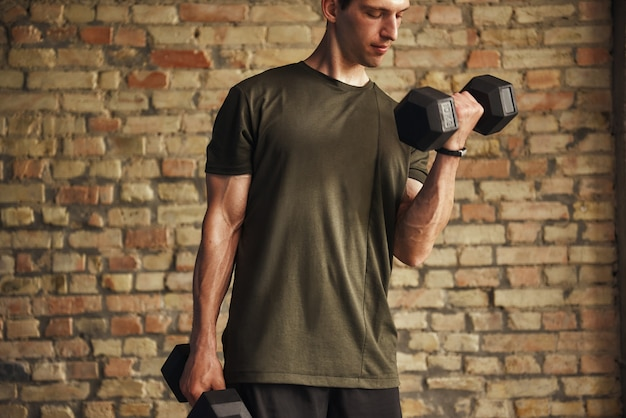 Homem bonito e atlético se exercitando com halteres em pé contra uma parede de tijolos na academia