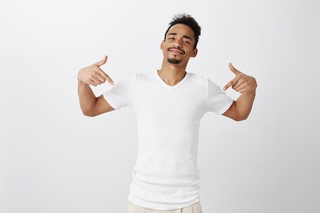 Homem bonito e atrevido de pele escura apontando o dedo para baixo, mostrando uma promoção e um link de clique convidativo