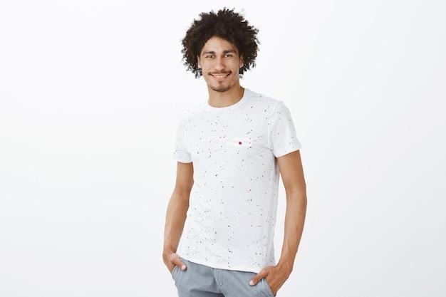 Homem bonito e atrevido sorrindo sobre uma parede branca, parecendo confiante