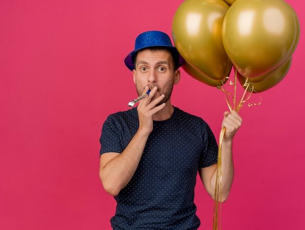 Homem bonito e bonito, caucasiano, impressionado, usando chapéu de festa azul segurando balões de hélio, soprando apito isolado em um fundo rosa com espaço de cópia
