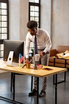 Homem bonito e bonito em pé à mesa enquanto termina seu trabalho