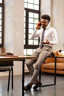 Homem bonito e bonito fazendo uma ligação enquanto está ocupado com o trabalho