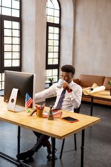 Homem bonito e bonito olhando para a tela do computador enquanto se concentra em seu trabalho