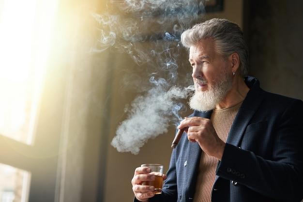 Homem bonito e brutal de meia idade com barba, olhando para longe, segurando o charuto e o copo de uísque, de pé no interior do loft. estilo de vida, sucesso, conceito de pessoas