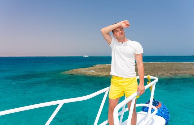Homem bonito e cansado no iate em um dia ensolarado de verão, lindo mar turquesa no fundo