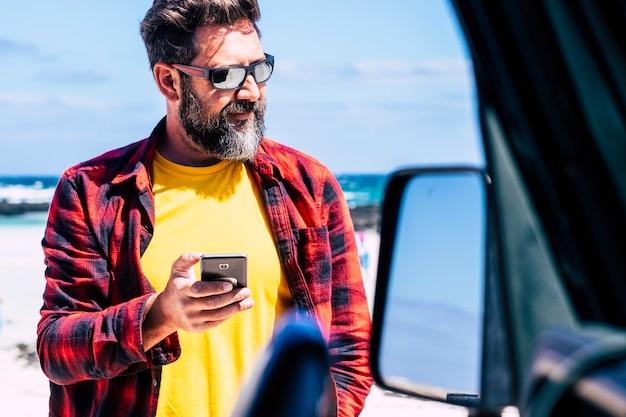 Homem bonito e caucasiano com barba usando um telefone moderno fora do carro com a praia e as ondas do mar em cena