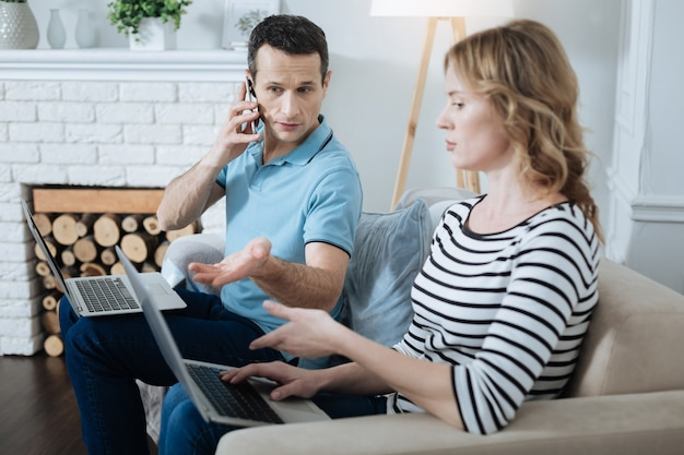 Homem bonito e concentrado de cabelos escuros falando ao telefone, trabalhando em seu laptop e discutindo trabalho com sua esposa