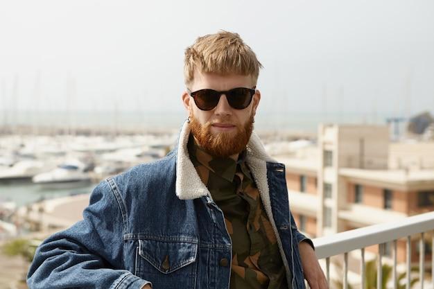 Homem bonito e confiante com barba difusa em pé no ponto de vista com os braços nos trilhos da cerca branca