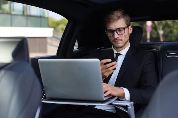 Homem bonito e confiante em terno completo, olhando para seu telefone inteligente enquanto está sentado no carro e usando o laptop.
