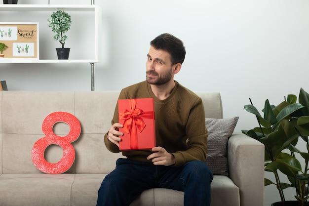 Homem bonito e confiante segurando uma caixa de presente vermelha e olhando para a frente, sentado no sofá na sala de estar em março, dia internacional da mulher