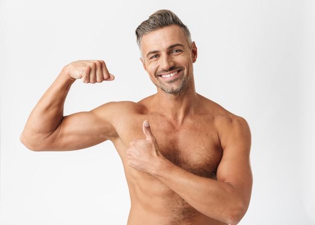 Homem bonito e confiante sem camisa, isolado no branco, flexionando os bíceps com o polegar para cima