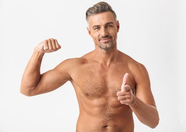Homem bonito e confiante sem camisa, isolado no branco, flexionando os bíceps