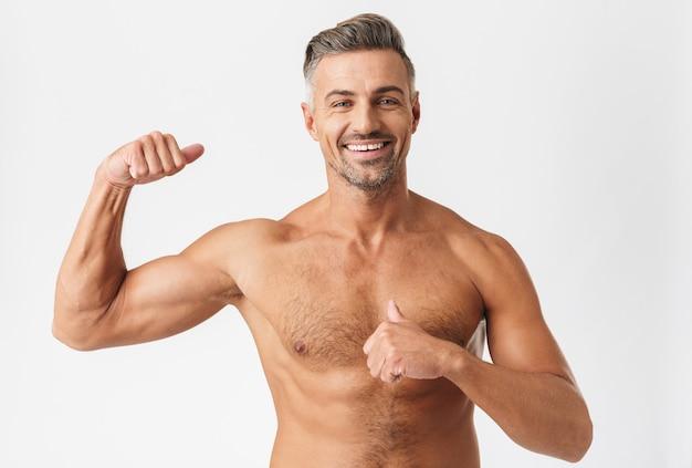 Homem bonito e confiante sem camisa parado isolado no branco, flexionando os bíceps, apontando para si mesmo