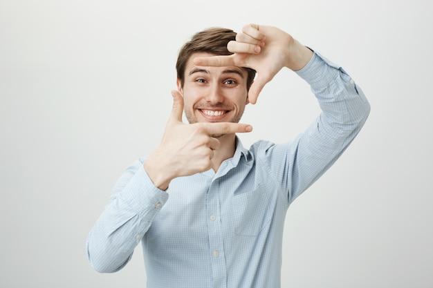 Homem bonito e criativo sorrindo, mostrando molduras de mão, momento de captura