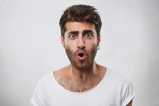 Homem bonito e elegante com barba usando brinco e camiseta branca, olhos e boca bem abertos expressando sua surpresa e choque