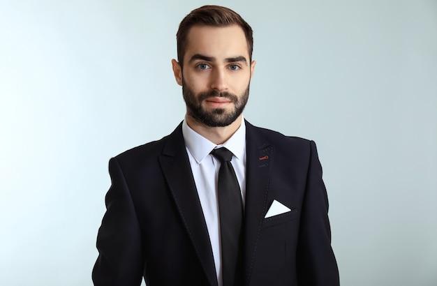 Homem bonito e elegante com roupas formais contra um fundo claro