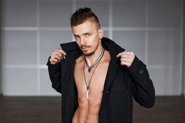 Homem bonito e elegante com torso nu e casaco preto