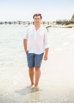 Homem bonito e elegante de camisa branca, caminhando à beira-mar