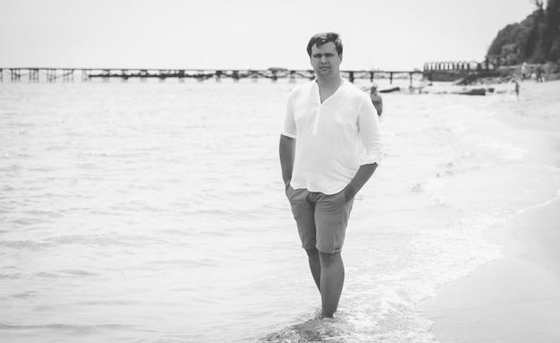 Homem bonito e elegante em pé no mar
