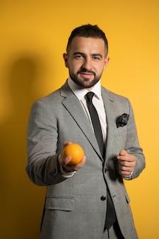 Homem bonito e elegante em um terno cinza usando óculos estende a mão e oferece laranja em uma das mãos, isolado na parede amarela
