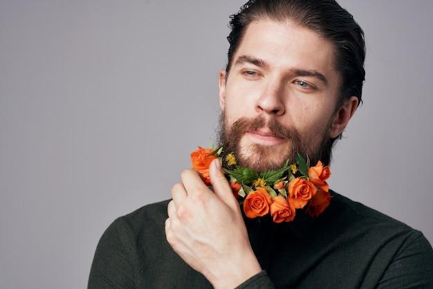 Homem bonito e elegante em uma camisa preta flores em uma parede cinza barba decoração romance.