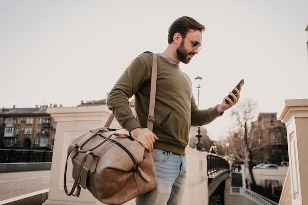 Homem bonito e elegante hippie andando na rua da cidade com uma bolsa de couro usando o aplicativo de navegação do telefone, viagem vestindo moletom e óculos escuros, tendência de estilo urbano