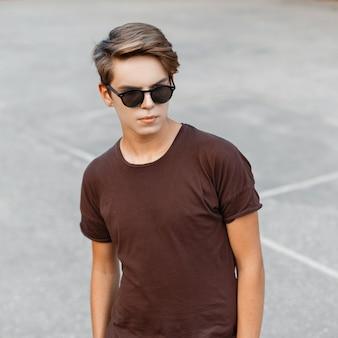 Homem bonito e elegante jovem hippie com um penteado estiloso em uma camiseta marrom da moda com óculos de sol da moda na quadra de basquete