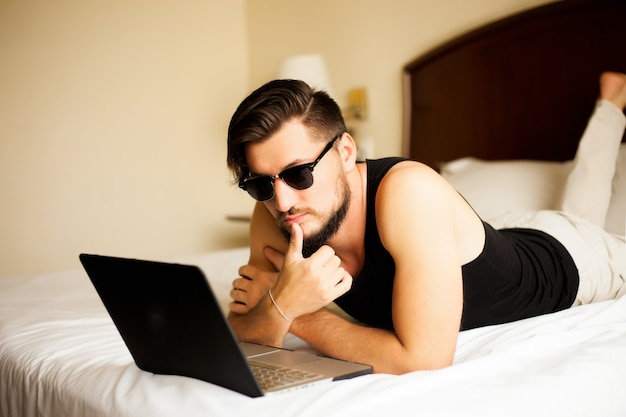 Homem bonito e elegante posando ao ar livre em um hotel, deitado na cama