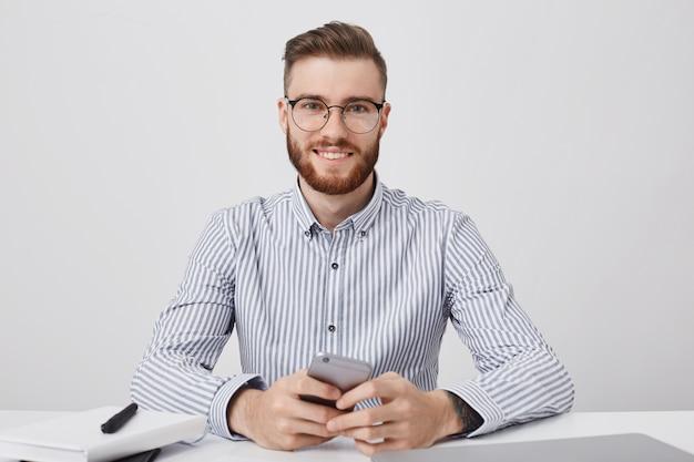 Homem bonito e elegante vestido de maneira formal, sentado à mesa de trabalho e usando smartphone para ler notícias online