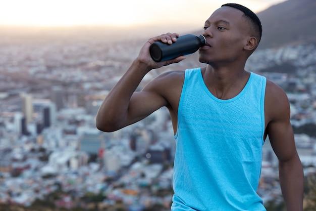 Homem bonito e em forma sente sede, bebe água da garrafa, tem pele negra, precisa recuperar forças, usa colete casual, posa alto contra a cidade borrada, fez corrida matinal cansativa.