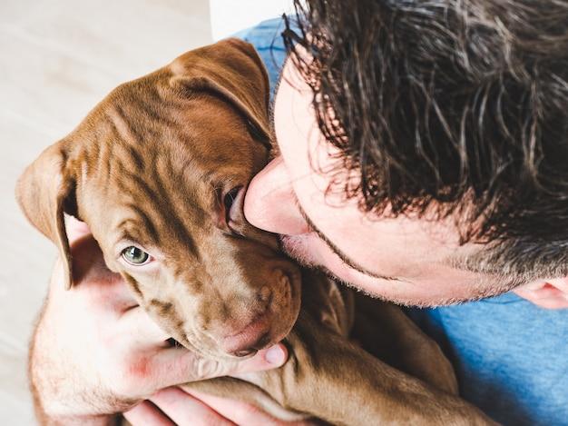 Homem bonito e encantador cachorrinho.
