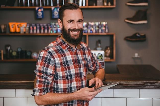 Homem bonito e feliz com barba em camisa xadrez usando tablet na barbearia