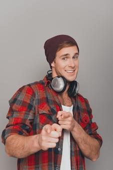 Homem bonito e feliz com tampa e protetores de ouvido apontando para a câmera