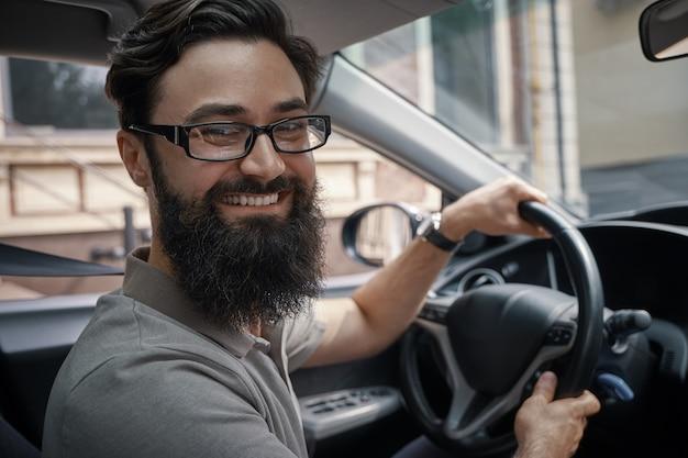 Homem bonito e feliz dirigindo o carro