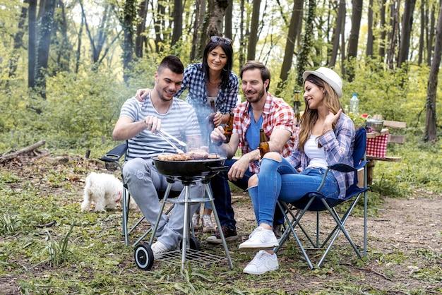 Homem bonito e feliz preparando churrasco ao ar livre para amigos