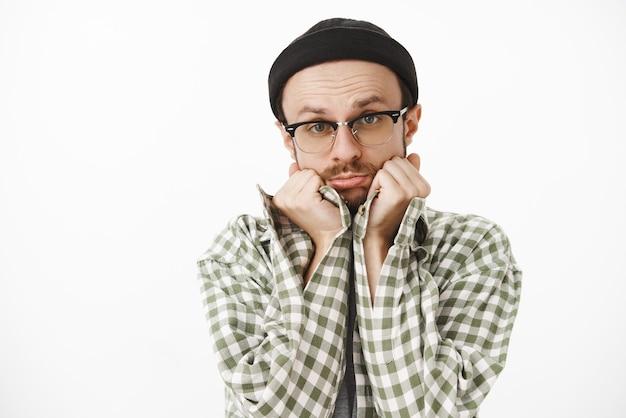Homem bonito e fofo com óculos de gorro preto e camisa xadrez verde inclinando a cabeça nas palmas das mãos fazendo beicinho e dobrando os lábios fazendo um olhar terno e inocente