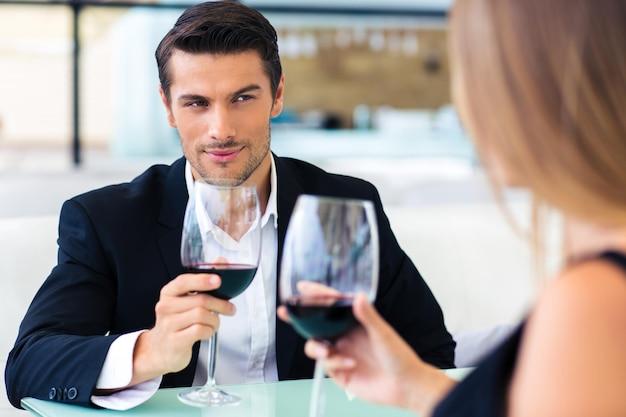 Homem bonito e formal bebendo vinho tinto com a namorada em restaurante