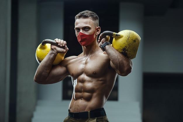 Homem bonito e forte e musculoso, caucasiano, fazendo exercícios na academia usando uma máscara durante o treino com kettlebell